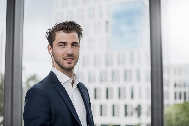 Ritratto di giovane uomo d'affari fiducioso indossare auricolari alla finestra — Foto stock