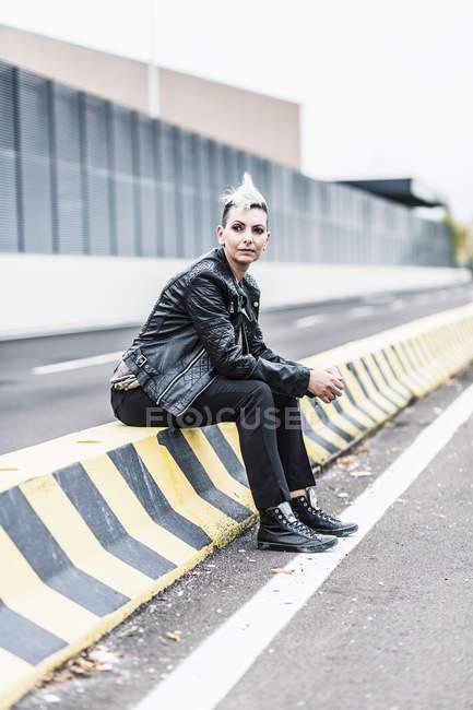 Панк-женщина, сидящая на обочине, оглядывается по сторонам — стоковое фото