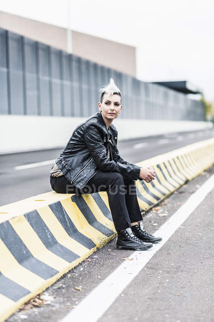 Punk woman sitting at roadside looking around — Stock Photo