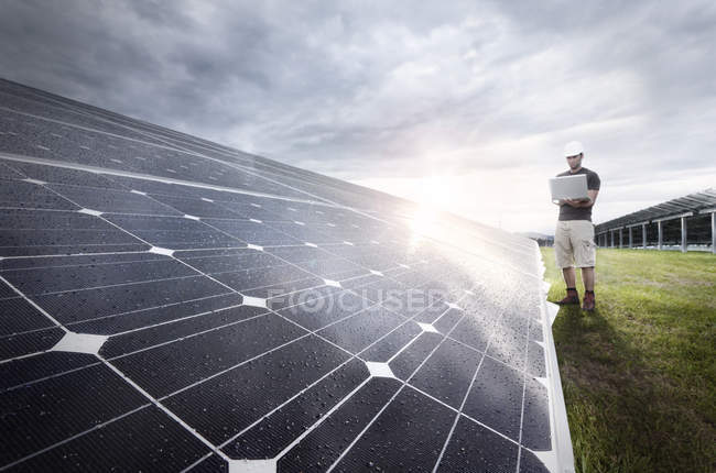 Engineer with laptop checking solar plant at evening twilight — Stock Photo