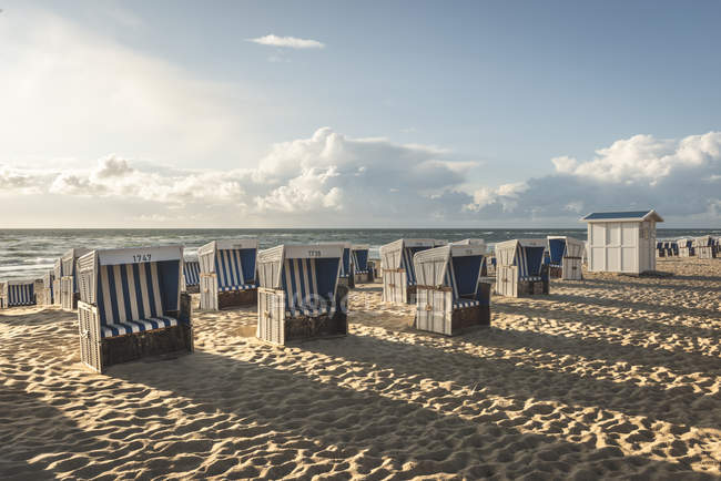 Germany, Schleswig-Holstein, Sylt, Westerland, hooded beach chairs on beach — Stock Photo