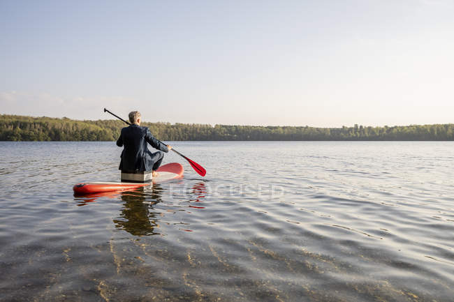 Opinião traseira o homem de negócios que rema no lago — Fotografia de Stock