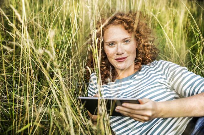 Retrato de jovem sorridente relaxando na grama com tablet — Fotografia de Stock