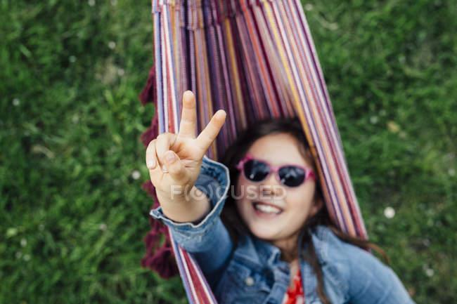 Усміхнена дівчина носить сонцезахисні окуляри лежачи в гамаку показуючи знак перемоги — стокове фото