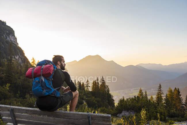 Austria, Tirolo, Escursionista in pausa, seduto sulla panchina, guardando la vista — Foto stock
