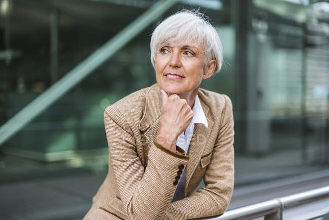 Portrait of senior businesswoman leaning on railing in city and looking around — Stock Photo