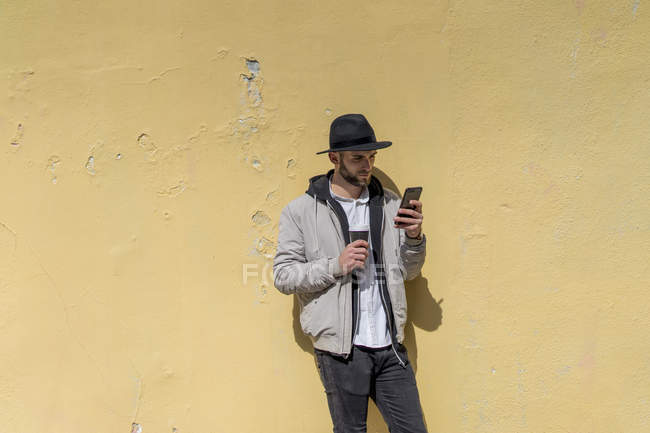 Bearded man wearing black hat, leaning on wall, using smartphone, coffee to go — Stock Photo