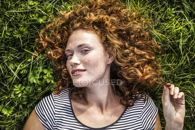Portrait d'une jeune femme souriante allongée sur une prairie verte — Photo de stock