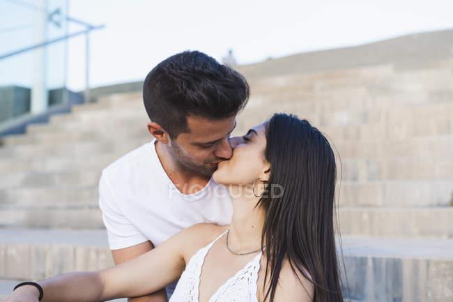 Junges romantisches Paar küsst sich auf Treppen im Freien — Stockfoto