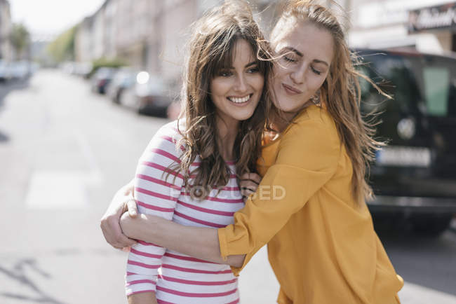 Two happy girlfriends embracing in the city — Stock Photo
