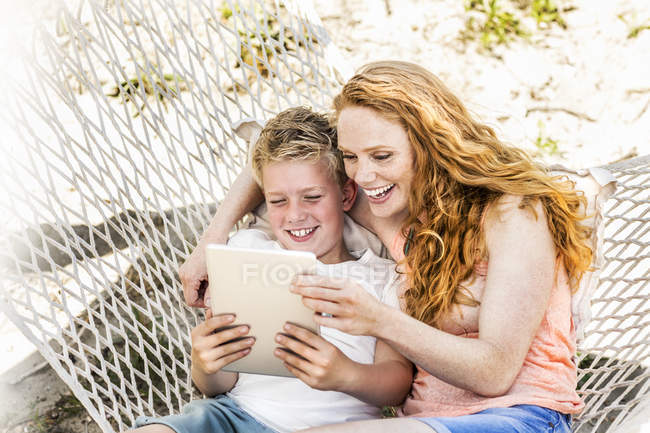 Happy mother and son in hammock looking at tablet — Stock Photo