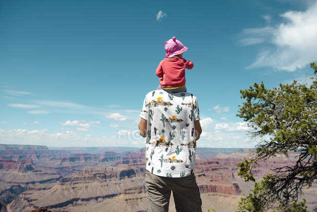 USA, Arizona, Grand Canyon National Park, father and baby girl enjoying the view, carrying on shoulders, rear view — Stock Photo