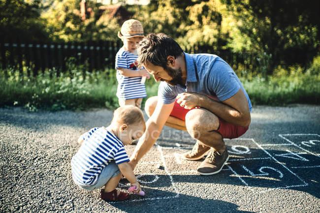 Padre dibujando Hopscotch sobre asfalto - foto de stock