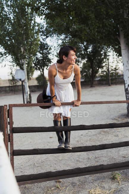 Портрет щаслива жінка з шолом їзда спираючись на ворота Верхова кільце — стокове фото