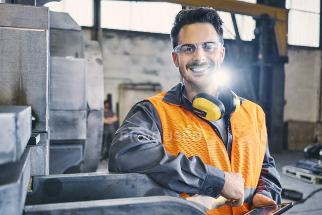 Portrait of smiling man wearing protective workwear and holding tablet in factory — Stock Photo