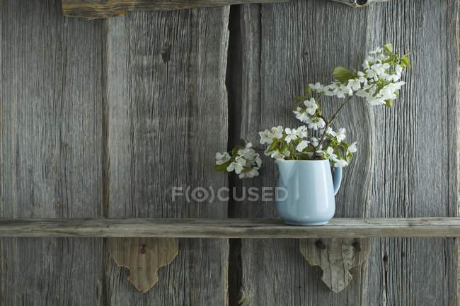 Ramita de flores de cerezo en tarro en estante, frente a pared de madera rústica - foto de stock