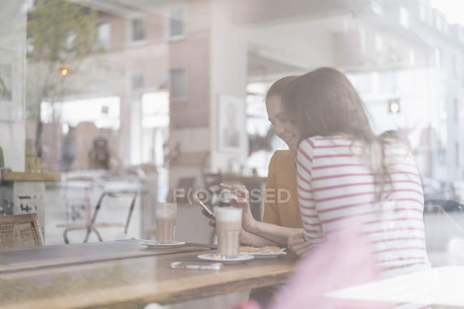 Two girlfriends meeting in a coffee shop, using smartphone — Stock Photo