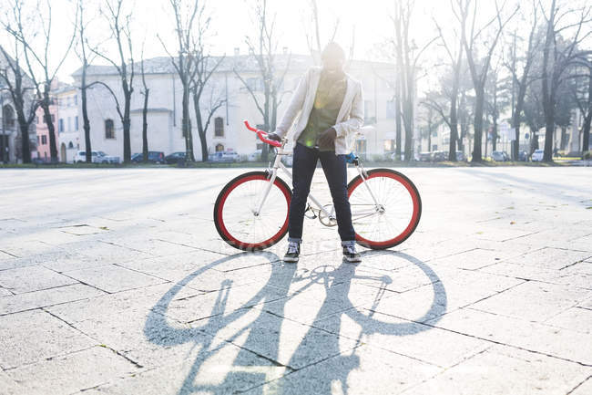 Young man standing with bicycle on urban square — Stock Photo