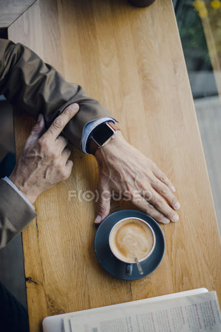 Mature businessman sitting in coffee shop, checking time — Photo de stock