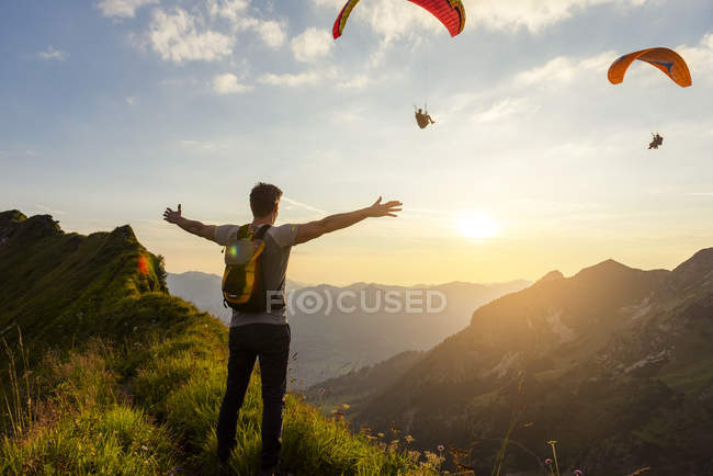 Man hiking in mountains at sunset, parachutists in sky — Stock Photo