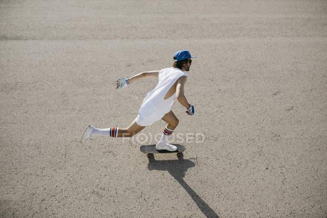Homme sportif élégant faisant du skateboard sur le tarmac — Photo de stock