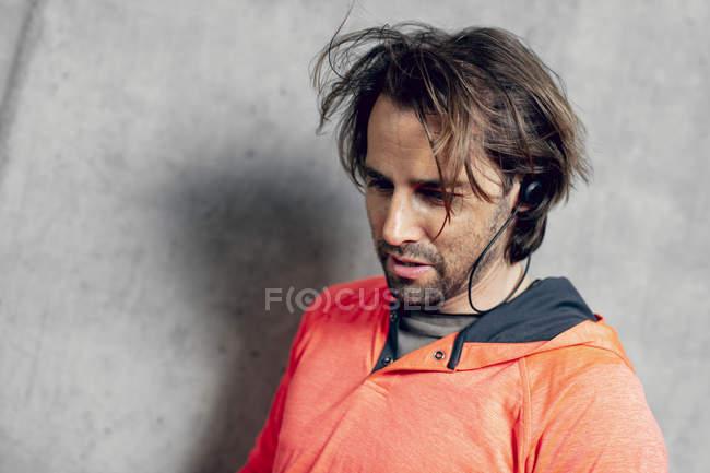 Verticale d'athlète utilisant des écouteurs au mur en béton — Photo de stock