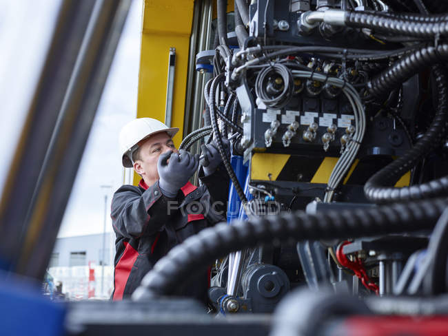 Worker fixing hose line with screw wrench — Stockfoto