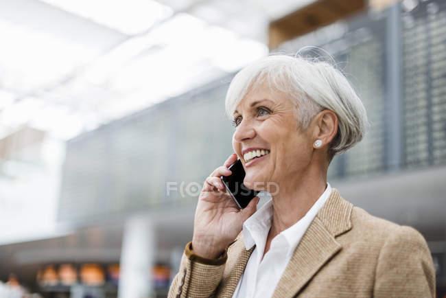 Smiling senior businesswoman en el teléfono celular en el aeropuerto - foto de stock