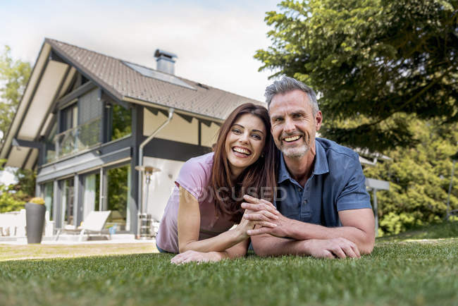 Portrait of happy couple lying in garden of their home — Stock Photo