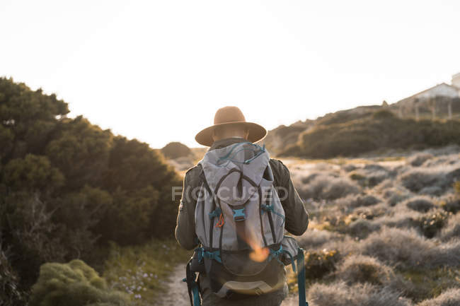 Italy, Sardinia, back view of hiker with hat and backpack — Stock Photo