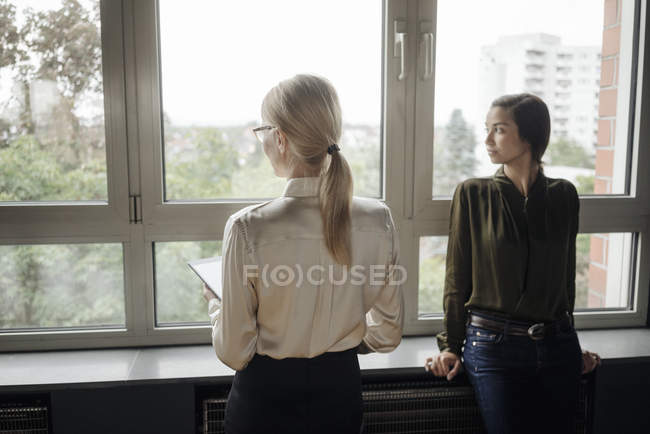 Two businesswomen in office looking out of window — Stock Photo