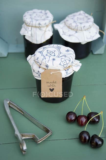 Lunettes de confiture de cerises maison, cerises et décapant de fosse — Photo de stock