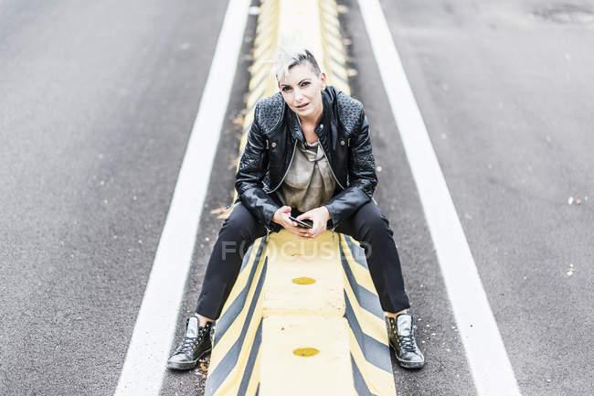 Portrait de punk femme assise au bord de la route tenant téléphone portable — Photo de stock