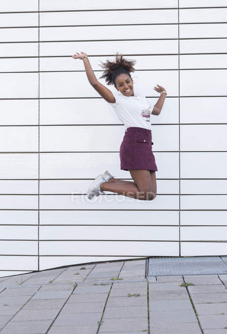 Verticale de jeune fille américaine africaine de sourire d'étudiant sautant dans l'air — Photo de stock