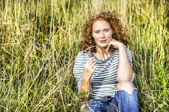 Портрет молодой женщины, сидящей на зеленом лугу — стоковое фото