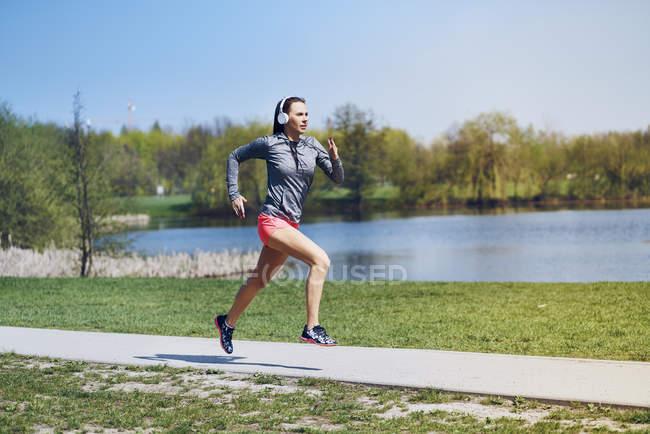 Female jogger running at park — Stock Photo
