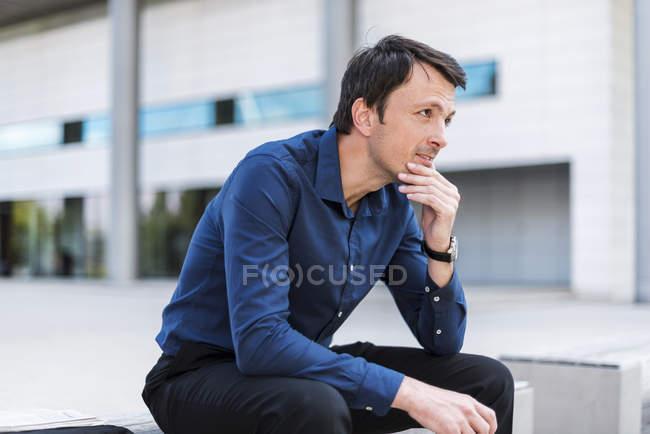 Homme d'affaires assis dehors pensant — Photo de stock
