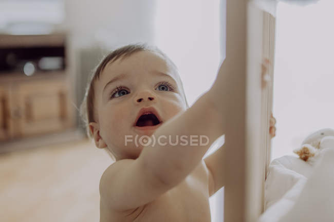 Little boy holding on to crib at home — Stock Photo