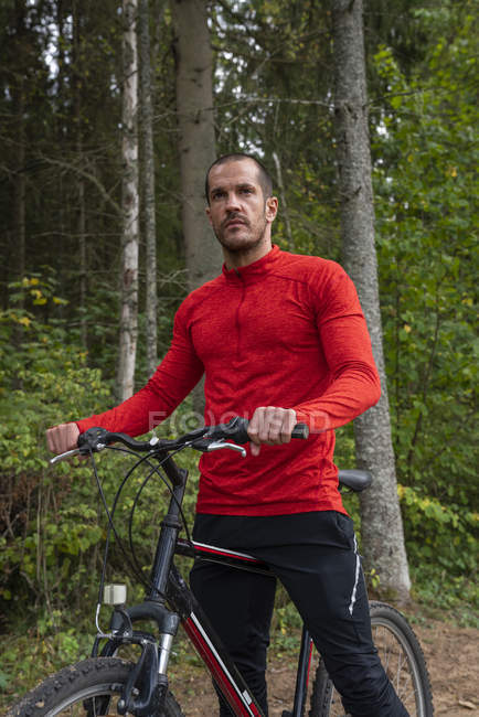 Male athlete mountain biking in woods — Stock Photo