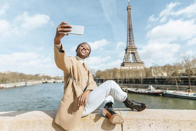Франция, Париж, Женщина, сидящая на мосту через реку Сена с Эйфелевой башней на заднем плане делает селфи на мобильном телефоне — стоковое фото