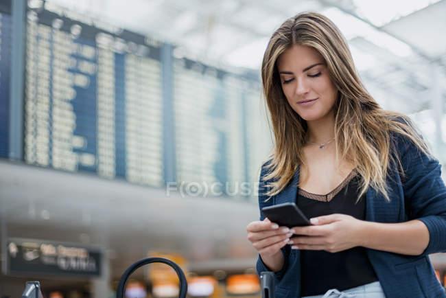 Молодая женщина, используя мобильный телефон на борту вылета оглядывается вокруг — стоковое фото