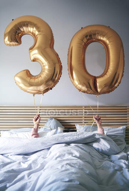 Woman with golden balloons celebrating birthday in bed — Stock Photo