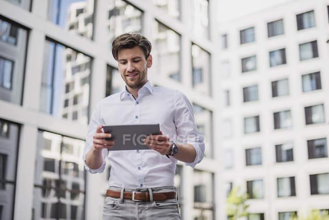 Uomo d'affari sorridente in città utilizzando tablet — Foto stock