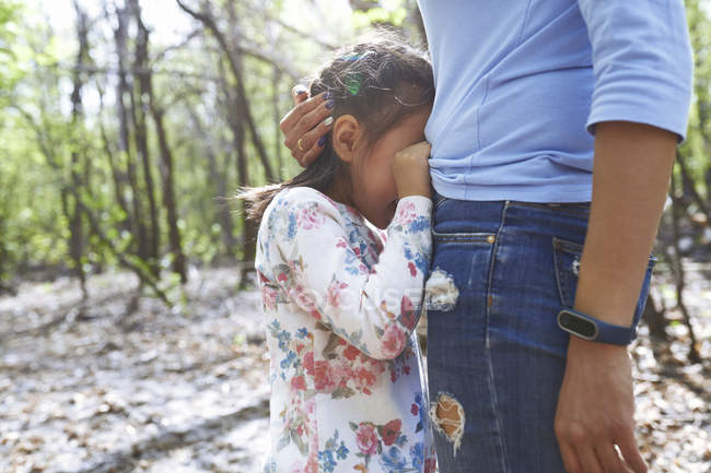 Daughter hiding at mother belly in a park — Stock Photo