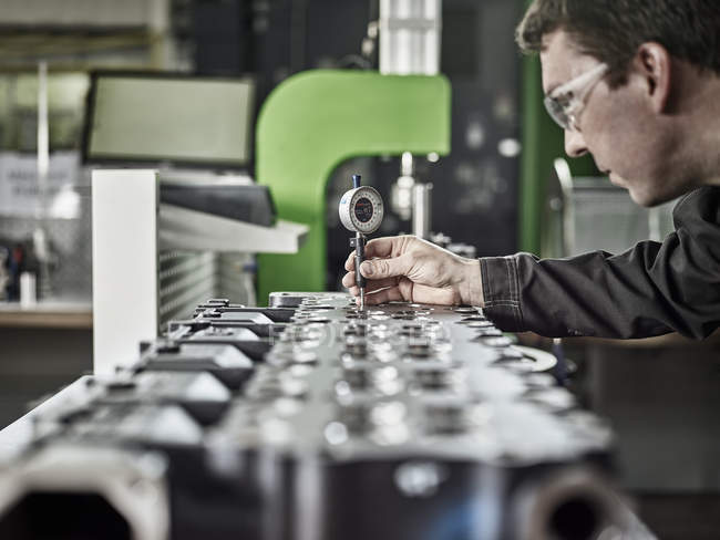 Worker in metalworking factory controlling cylinder head — стокове фото