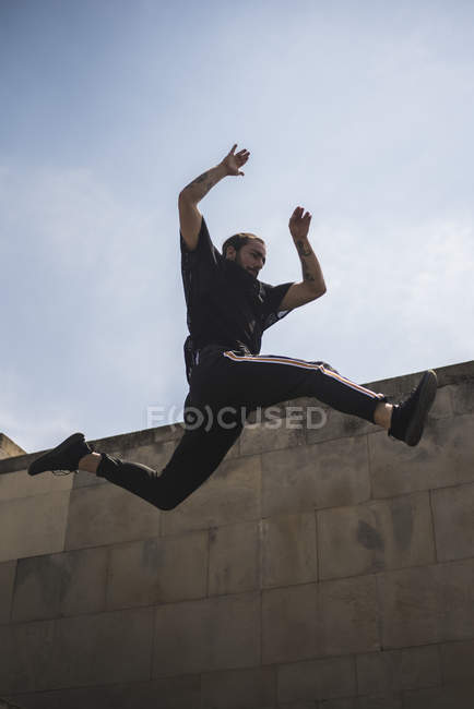Tattooed man doing parkour — Stock Photo