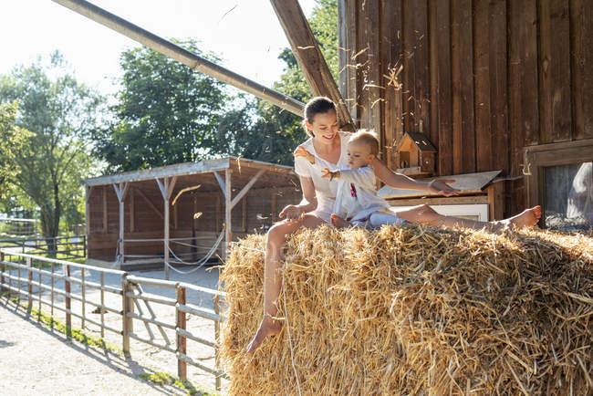 Felice madre e piccola figlia che giocano con la paglia in un fienile — Foto stock