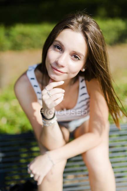 Портрет усміхнена молода жінка сидить на лавці — стокове фото
