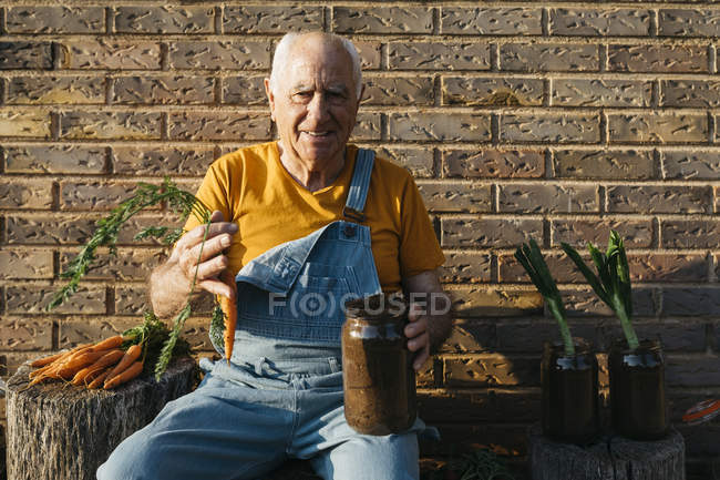 Smiling senior man with glass jar of soil and fresh carrot looking at camera — Foto stock