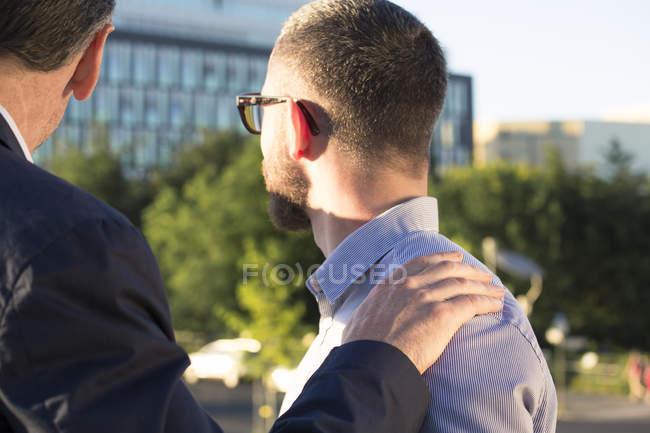 Older businessman placing hand on shoulder of younger businessman — Photo de stock